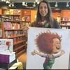 Annie Boulanger est dans une librairies et tient dans ses mains une affiche avec un dessin de Lili macaroni.