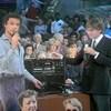 L'animateur Jacques Boulanger chante au micro à l'aide d'un appareil à cassettes de karaoké devant le public réuni au Complexe Desjardins. À ses côtés, un représentant de la compagnie Panasonic.