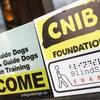 Une enseigne dans la vitre d'un commerce indique que l'application mobile du CNIB peut y être utilisée.