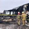 Des pompiers observent les décombres d'un bâtiment après un feu.