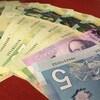 Plan serré de billets de monnaie canadienne reposant en éventail sur une table.