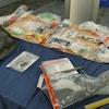 Des armes dans des sacs de plastique sur une table.