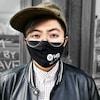 Ashley Au porte un masque devant un bâtiment, où il est inscrit qu'un concert de jazz aura lieu.