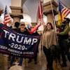 Des manifestants tiennent des drapeaux, notamment des États-Unis et à l'effigie de Trump.