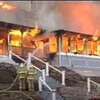 Flammes qui sortent des fenêtres de l'auberge et pompiers qui arrosent le brasier.