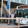 Un autobus blanc est garé. Des hommes et des femmes en descendent.
