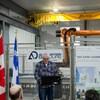 Le fondateur de l'entreprise, Bernard D'Amours, devant les nouveaux locaux et un projet de robot en montage dans l'atelier.