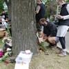 Des gens déposent des fleurs près d'un arbre.