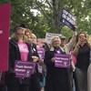 Des femmes tiennent des affiches dans leurs mains devant le parlement.