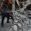 Un homme se penche dans les décombres d'une maison pour ramasser un morceau des débris.