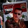 Un jeune garçon passe près d'une bannière où figure le portrait de Bachar Al-Assad.