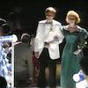 Deux jeunes habillés en tenue de soirée se tiennent par le bras et défilent devant des invités.