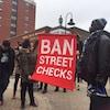 Des manifestants exhibent une bannière « Ban Street Checks » le 30 mars 2019 devant une bibliothèque d'Halifax.