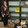 Une femme pose devant des étagères vides. À ses pieds se trouve des boîtes remplies de denrées non périssables.