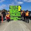Des hommes et des femmes autochtones bloquent une autoroute en brandissant des pancartes.