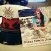 La photo d'un homme avec ses dates de naissance et de mort, posée à côté de sa casquette de pompier.
