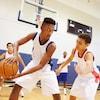 De jeunes hommes de l'école secondaire jouent au basketball dans un gymnase.