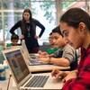 Des élèves regardent leurs ordinateurs dans une classe.