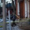 L'entrée d'une résidence avec un policier qui passe sous un ruban jaune qui bloque l'accès à la porte.