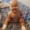 Un bébé assis sur un lit. Il sourit.