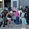Deux hommes sont arrêtés par des policiers et trois femmes essaient de parler à des policiers en tenue antiémeute.