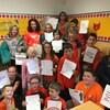 Un groupe d'une vingtaine d'élèves portant des vêtements de couleur orange montre une feuille de papier qui affiche le nombre de minutes de lecture qu'ils ont faite.