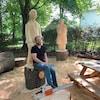 Un homme devant des sculptures.