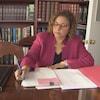 Bernadette Clément, la mairesse de Cornwall signe des papiers assise à une table.