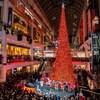 Un sapin de noël au milieu d'un centre commercial avec des centaines de personnes