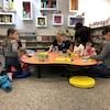 Des tous petits et des parents jouent à des jeux de société. Ils sont assis autour d'une table.