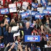 Entouré de Kamala Harris et de Gretchen Whitmer, Joe Biden lève les bras devant une foule de partisans, dont certains tiennent des affiches invitant à voter pour le candidat démocrate.