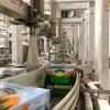 Des caisses de bière Resilience IPA sur un tapis roulant.