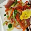 Des légumes et une fleur comestible rassemblés dans une assiette.