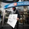Des manifestants à la Banque de Montréal tenant une enseigne sur laquelle on lit « Non, BMO! » en anglais.