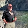 Bob Costa tient une canne à pêche sur le bord d'une rivière.