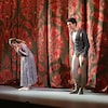 Une femme et un homme s'inclinent devant les spectateurs alors que le rideau de la scène est fermé derrière eux.