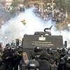 De la fumée s'élève entre des membres des forces de l'ordre portant un casque et des manifestants. Un drapeau de la Bolivie surgit au milieu de la fumée.