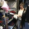 Une femme manipule des vêtements dans un entrepôt.