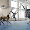 Capture d'écran d'une vidéo montrant le robot-chien Spot et deux robots bipèdes Atlas de Boston Dynamics se déhancher dans un gymnase.