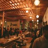 Des gens sont assis à des tables et au comptoir à l'intérieur d,une brasserie avec des lumières tamisées.
