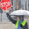 Une brigadière tient un panneau d'arrêt et un parapluie, tout sourire sous la neige.