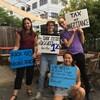 Des jeunes tiennent des pancartes sur lesquelles sont écrits en anglais divers slogans réclamant une plus grande taxation des riches.
