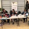 Trois femmes sont installées à une table dans un marché et tricottent.