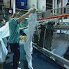 Deux femmes avec de grands draps devant une machine industrielle.