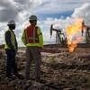 Deux travailleurs regardent des puits de pétrole.
