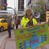 Vue sur un homme qui tient une pancarte dans la rue et un mégaphone.