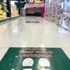 Un autocollant apposé au sol dans un supermarché demande aux clients de respecter les mesures de distanciation physique.