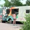 Le camion de cuisine de rue Crêpe là!, dans un parc. Une cliente attend son repas.