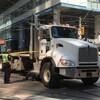 Photo d'un camion blanc immobilisé au milieu d'une intersection, entouré d'une banderole de police jaune.