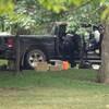 Deux agents fouillent le véhicule et en ont sorti des boîtes de carton, une glacière et un sac de poubelle en plastique.